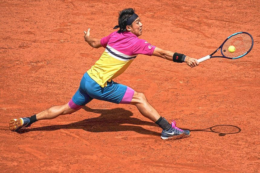 Japan's Kei Nishikori stretching for a backhand return to France's Jo-Wilfried Tsonga in their French Open second-round match in Paris yesterday. He recovered from a slow start to win 4-6, 6-4, 6-4, 6-4. PHOTO: AGENCE FRANCE-PRESSE