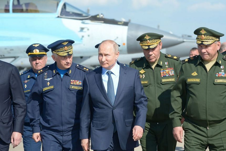 Russian President Vladimir Putin, surrounded by top military officers and officials, tours a military flight test centre in Akhtubinsk on May 14, 2019.
