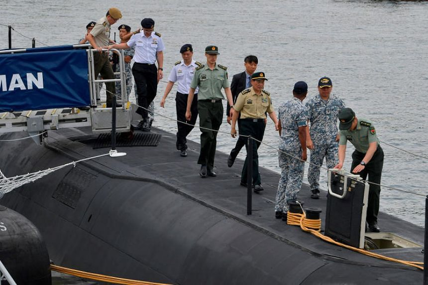 China Defence Minister Wei Fenghe (in brown) embarking the Archer-class submarine RSS Swordsman during his visit to RSS Singapura - Changi Naval Base, accompanied by (from left) Chief of Defence Force, Lieutenant-General Melvyn Ong and Chief of Navy,
