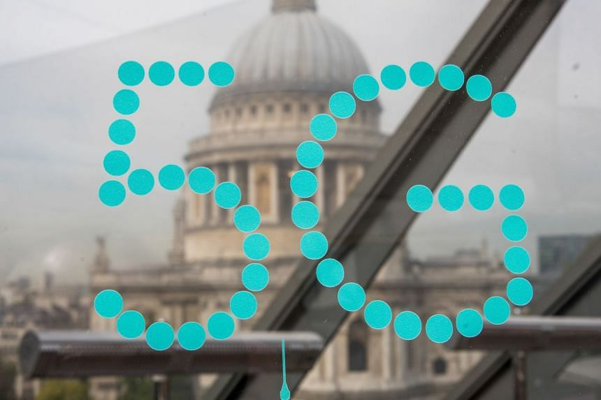 A 5G sign sits on a display in view of St Paul's Cathedral in London.
