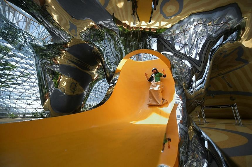 Left: One of the four slides at Canopy Park's Discovery Slides attraction, designed as an art sculpture as well as a space for play. Centre: The hedge maze, one of the park's two mazes spread out over 500 sq m. Below: Four-year-old Oliver Sim catchin