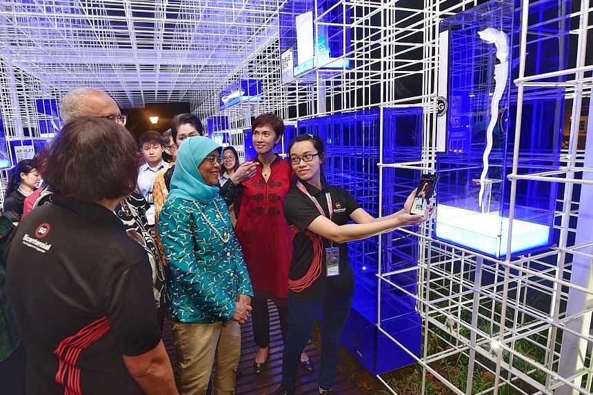 President Halimah Yacob, her husband Mohamed Abdullah Alhabshee and Manpower Minister Josephine Teo (in red), looking at a 3D-printed giant replica of a keris from 19th-century Palembang in South Sumatra. They were touring the Emporium of the East pa