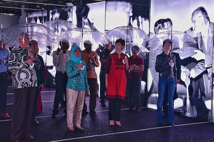 """Armed with umbrellas, President Halimah Yacob, her husband Mohamed Abdullah Alhabshee, Manpower Minister Josephine Teo (in red), and Mr Gene Tan (far right), executive director of the Singapore Bicentennial Office, kept the """"rain"""" at bay in the final"""
