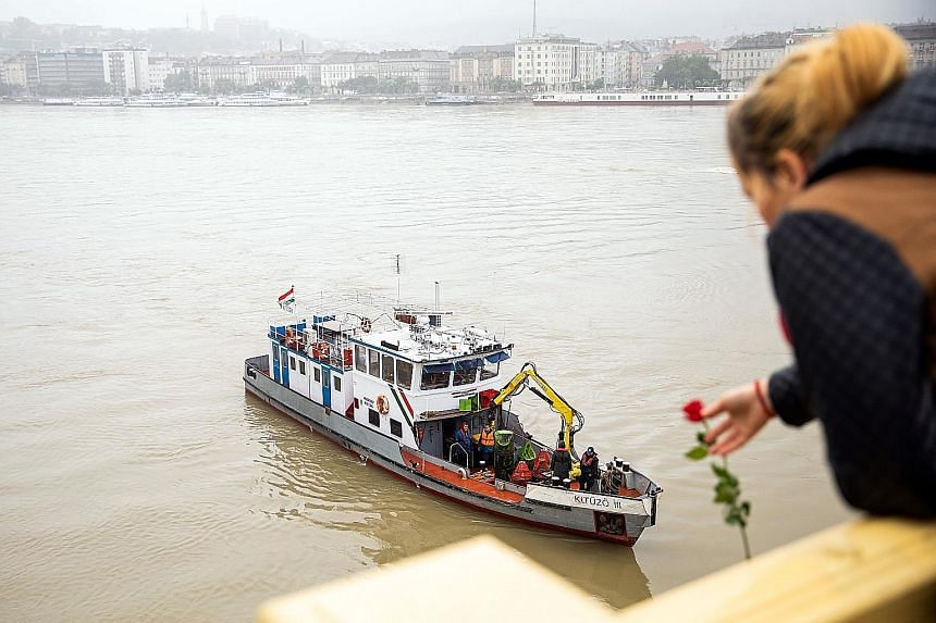 A woman throwing a flower from a bridge during a search of the Danube River in Budapest, Hungary, yesterday, following a collision of a hotel ship and a smaller cruise ship the previous evening. PHOTO: MTI