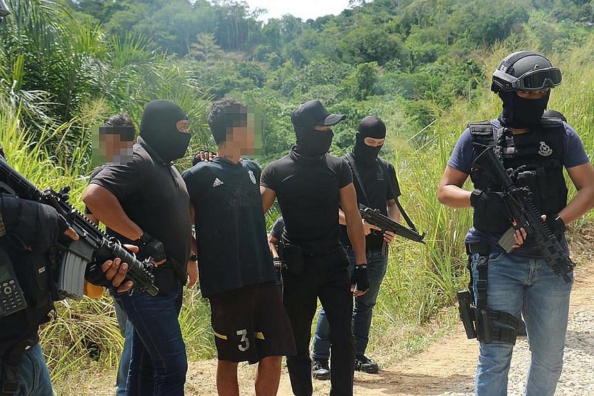 Malaysia's anti-terror police with a suspected militant during operations across three states between May 17 and yesterday. Three suspected ISIS militants - a Malaysian, an Indonesian and a Bangladeshi - were nabbed in Selangor, Sabah and Kedah respe