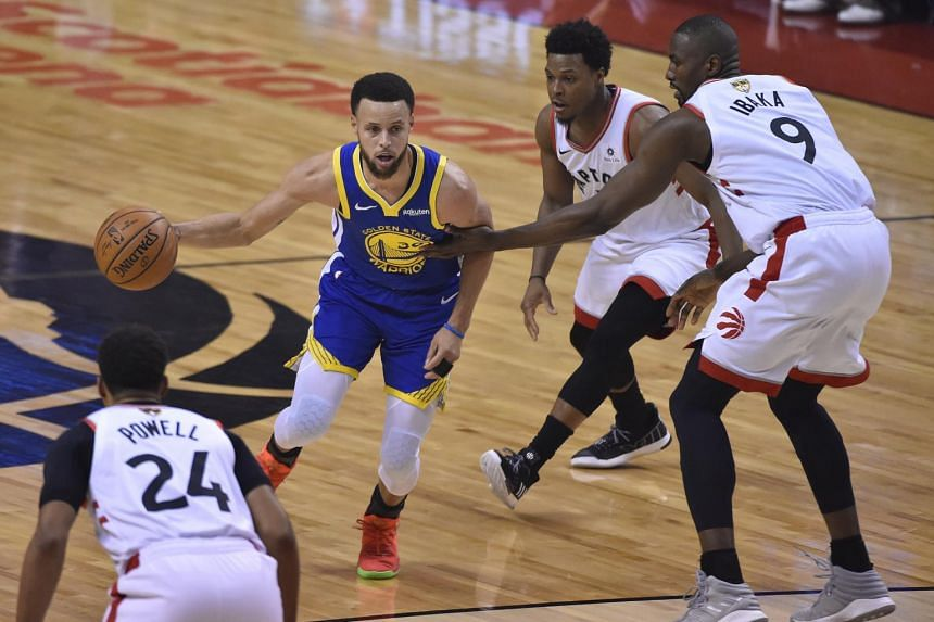 Golden State Warriors guard Stephen Curry (in blue) in action against the Toronto Raptors during the NBA Finals game one at Scotiabank Arena in Toronto, Canada, on May 30, 2019.