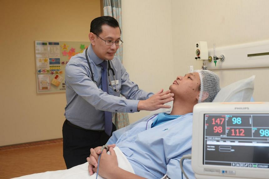 Adjunct Associate Professor Edwin Seet from Khoo Teck Puat Hospital checking a mock patient's airway prior to surgery.