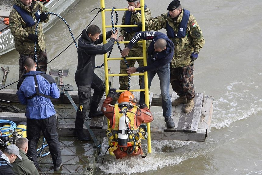 A diver descends a ladder as rescuers work after a boat capsized under Margaret Bridge, in Budapest, Hungary, on May 30, 2019.