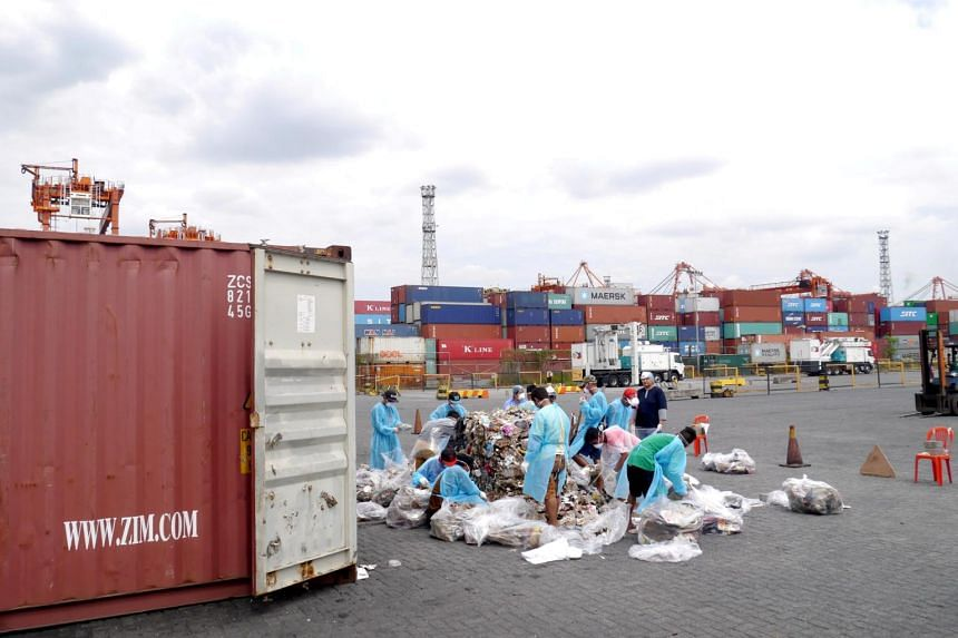 Philippine customs officials inspect cargo containers containing tonnes of garbage shipped by Canada at Manila port, on Nov 10, 2014.