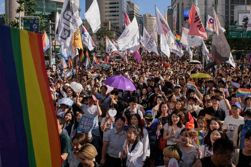 Participants of the Seoul Queer Parade marching along a street in Seoul on July 14, 2018.