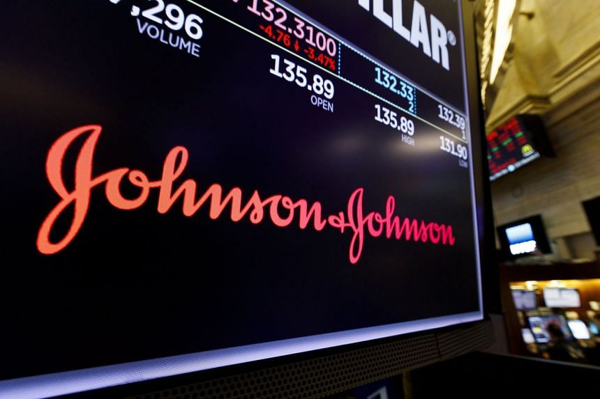 A screen shows the logo for Johnson and Johnson on the floor of the New York Stock Exchange.