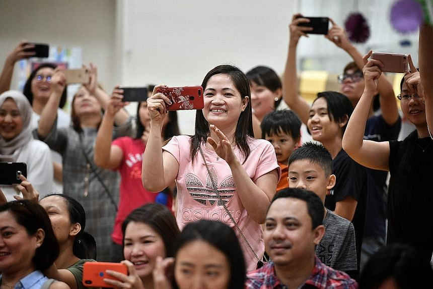 Ms Yusyie takes a photo of a performance by pre-schoolers.