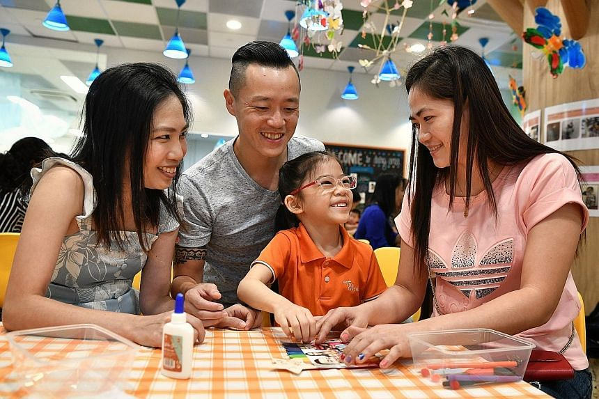 Parents Genevieve and Jeffrey Pang help daughter Sheena make a family photo frame for their helper Yusyie Quimada (right).