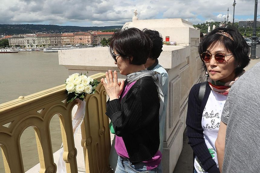 South Koreans mourning yesterday at a bridge over the Danube near the site of the accident involving a cruise ship and a tourist boat. Seven South Koreans were rescued, seven died, and 19 of their compatriots were among the 21 people still missing. P