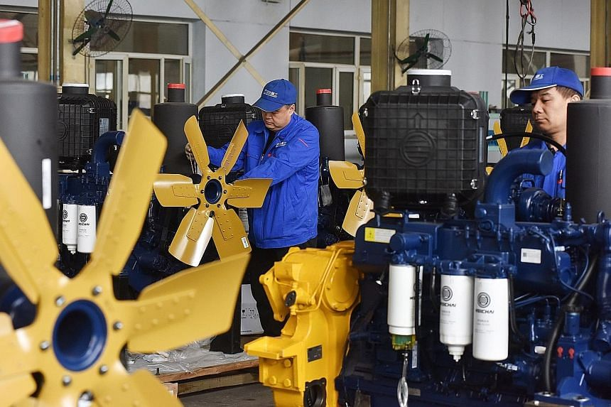 Employees working on bulldozer engines at a factory in Zhangjiakou in Hebei province. While the factory indicator has been in a gradual multi-year decline due to automation and younger people opting out of the sector, a sharp contraction in the peak