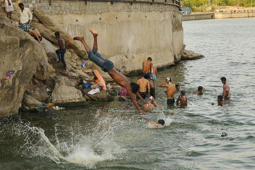 Indian youths take relief from the heat at the Ana Sagar lake in Ajmer, in the Indian state of Rajasthan on May 31, 2019.