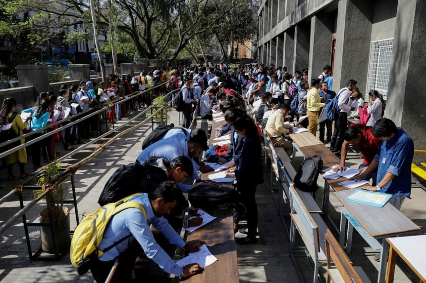 Job seekers fill up forms as others line up for registration during a job fair in Chinchwad, India.