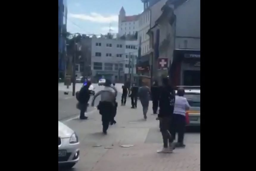Police run towards the assailant in a screenshot from a video of the incident uploaded to social media.