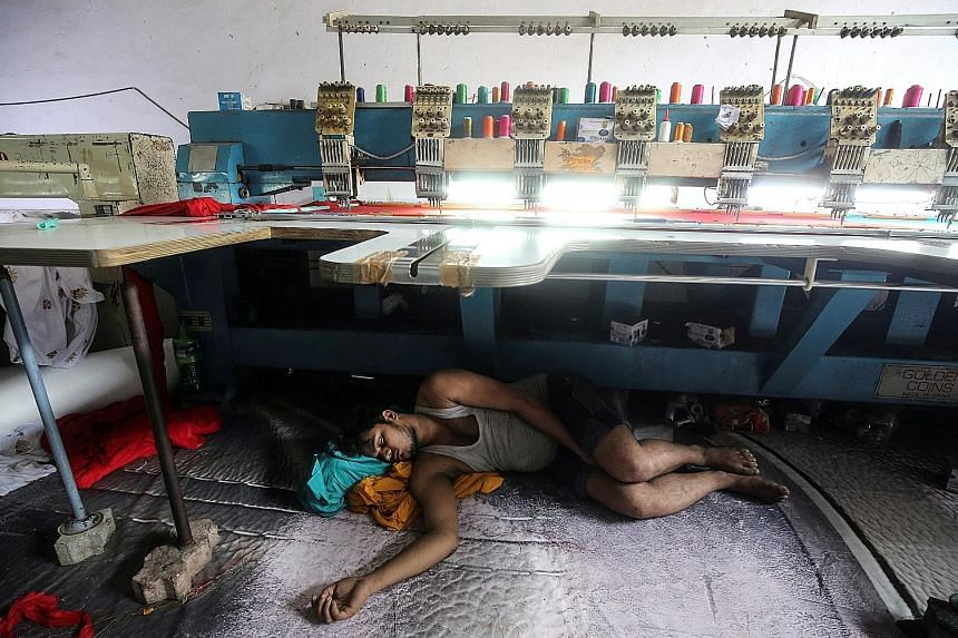 A worker sleeping under an embroidery machine in a workshop in Mumbai. The United States' decision to end preferential trade treatment for India comes as official figures show India's growth slowing for the third straight quarter to 5.8 per cent in J