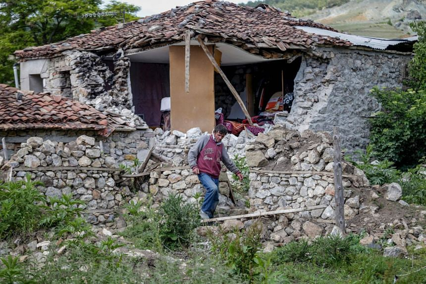 A man walks next to a damaged house after an earthquake rattled the area of the village of Floq.