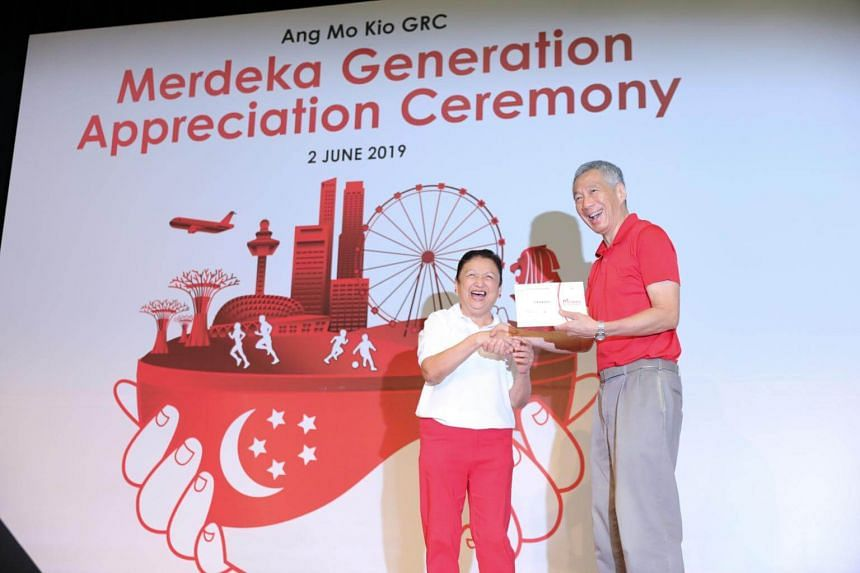 PM Lee Hsien Loong, who is himself part of the Merdeka Generation, receiving his welcome folder from Madam Noelene De Foe, 66, who chairs the Teck Ghee Community Club Management Committee.