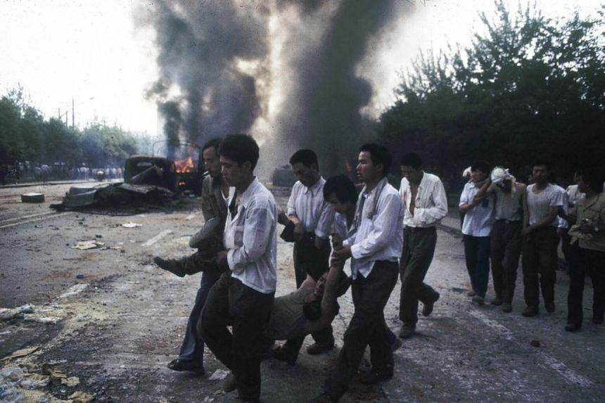 Wounded plainclothes officers on West Chang'An Avenue after Chinese forces clashed with students while enforcing martial law, during the Tiananmen Square Protest in Beijing in 1989.