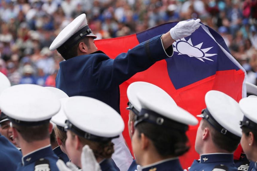 A graduate waves the Taiwanese flag during commencement ceremonies at the US Air Force Academy in Colorado Springs, Colorado, on May 30, 2019.