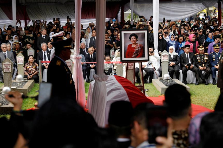 A portrait and the casket of the late former Indonesian First Lady Ani Yudhoyono seen during the funeral ceremony at Kalibata Heroes Cemetery complex in Jakarta on June 2, 2019.