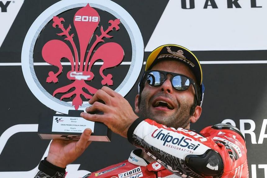 Danilo Petrucci holds his trophy as he celebrates on the podium after winning the Italian Moto GP Grand Prix at the Mugello race track on June 2, 2019.
