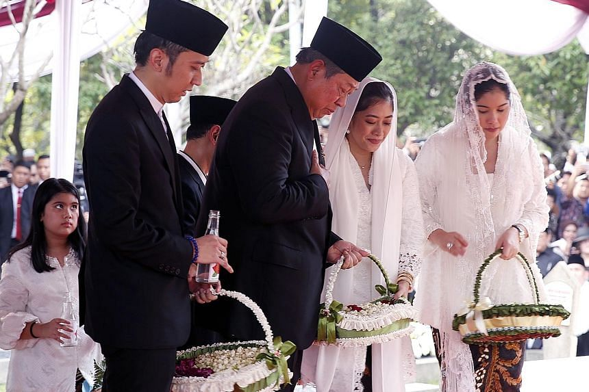 Above: Mrs Ani Yudhoyono was given a military funeral at Kalibata Heroes Cemetery in South Jakarta. Left: Former Indonesian president Susilo Bambang Yudhoyono, accompanied by his family members, laying flowers during his wife's funeral.