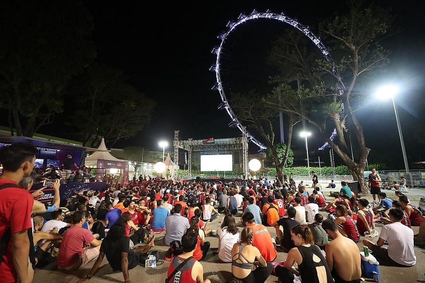 Above: Fans watching the final at the Sundown Marathon runners' village. Left: Reds fan Dinesh Kumar and father Dewadas Vellasamy, who supports Spurs, in Madrid.