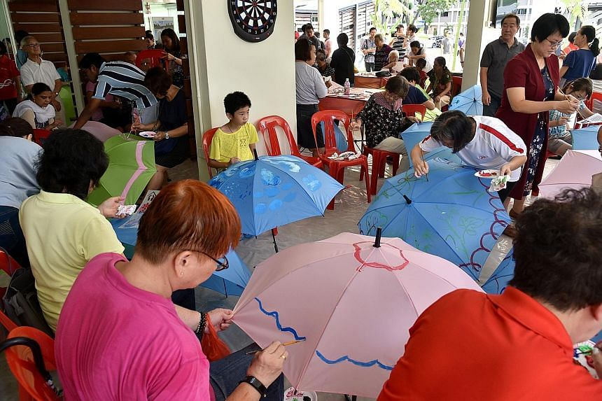 Participants painting umbrellas at a workshop held by Cheng San-Seletar Grassroots Organisations and Touch Community Services at the hub yesterday.