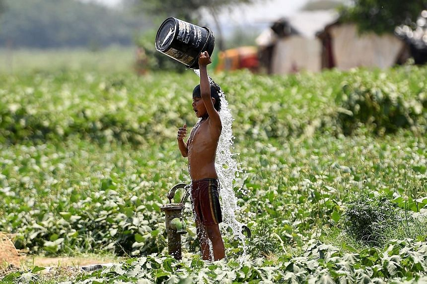An Indian boy trying to cool himself off amid rising temperatures in New Delhi last Wednesday. Several cities in Rajasthan were above 47 deg C. PHOTO: AGENCE FRANCE-PRESSE