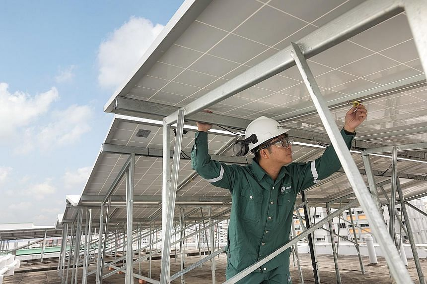 A Sembcorp Solar worker inspecting panels at one of Sembcorp's HDB rooftop project sites in Choa Chu Kang. Besides hiring contractors, Sembcorp employs about 35 workers in its solar team.