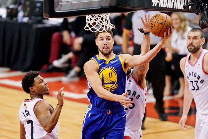 Golden State Warriors guard Klay Thompson (centre) shoots between Toronto Raptors players Kyle Lowry and Fred VanVleet during the 2019 NBA Finals at Scotiabank Arena on June 2, 2019.