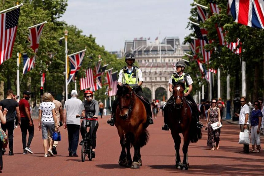 Police officers ride their horses as they patrol along the US and Union flag-lined Mall, leading to Buckingham Palace, in central London on June 2, 2019, ahead of a visit to the UK by US President Donald Trump.