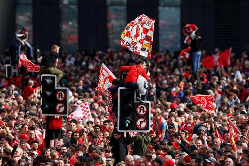 Liverpool fans sit on traffic lights during the victory parade on June 2, 2019.