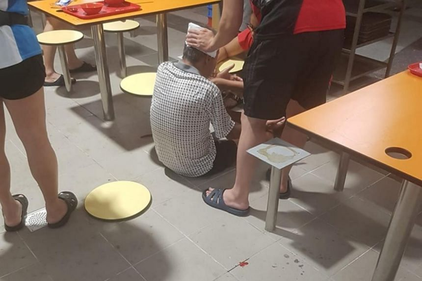 Spots of blood can be seen next to the man, who is sitting on the ground next to the seat of a chair that appears to have fallen apart from its base.