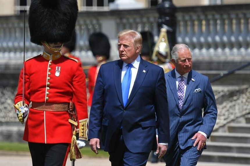 US President Donald Trump (centre), flanked by Britain's Prince Charles, Prince of Wales (right) arrives to inspect an honour guard during a welcome ceremony at Buckingham Palace in central London on June 3, 2019, on the first day of their three-day