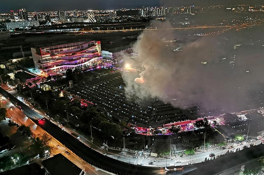 Above: Thick smoke rising into the night sky over Chatuchak weekend market in Bangkok on Sunday. Police are investigating the cause of the blaze. Left: Witnesses said they saw flames and heard sporadic explosions as strong winds fanned the fire.