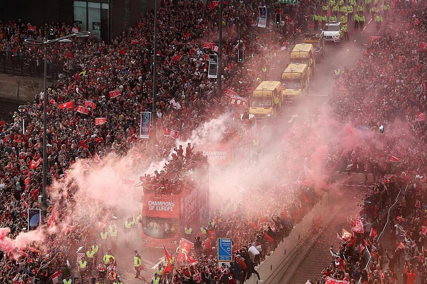 Liverpool supporters throng the streets during the Champions League victory parade on Sunday. The open-top bus escorted by local police and with the team on board inched through the city centre amid cheers and confetti.