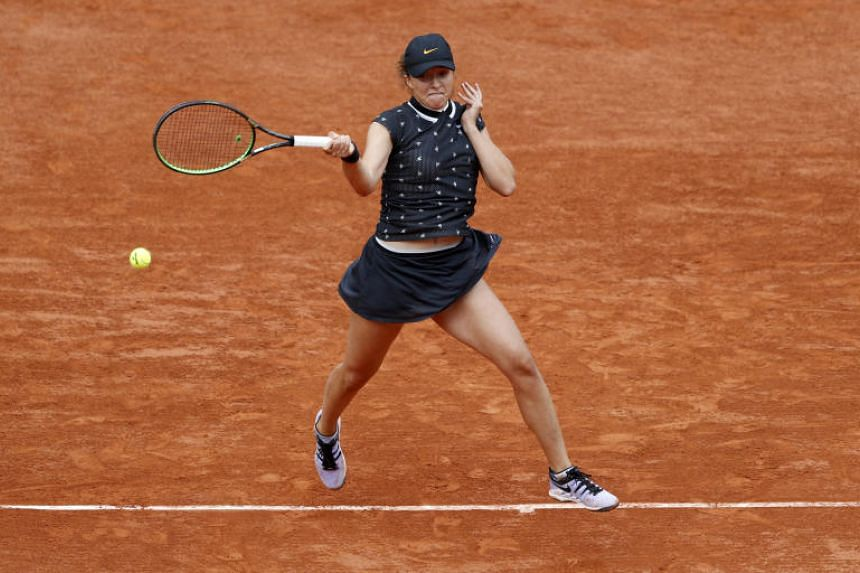 Poland's Iga Swiatek in action during her fourth round match against Romania's Simona Halep.