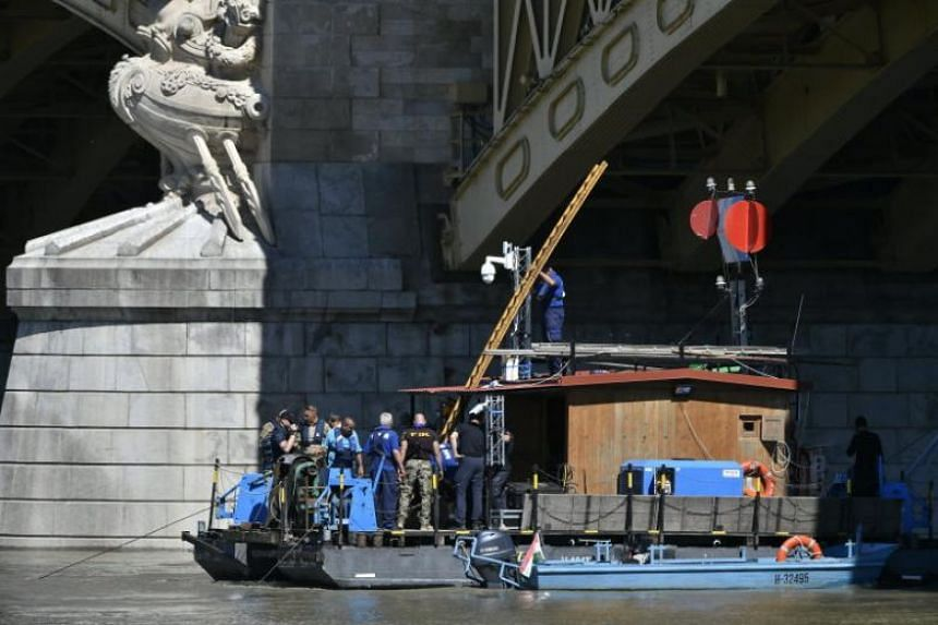 Members of the Hungarian rescue team work on a pontoon moored under Margaret Bridge, as operations to prepare the recovery of the capsized boat continue in Budapest on June 3, 2019.