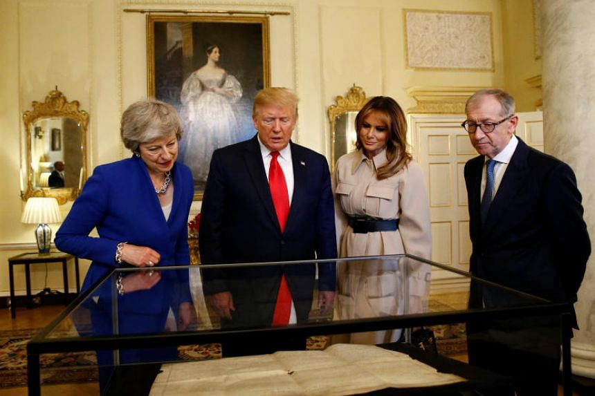 (From left) British Prime Minister Theresa May, US President Donald Trump, his wife Melania and Mrs May's husband Philip viewing a handwritten parchment copy of the US Declaration of Independence at Mrs May's office on June 4, 2019.