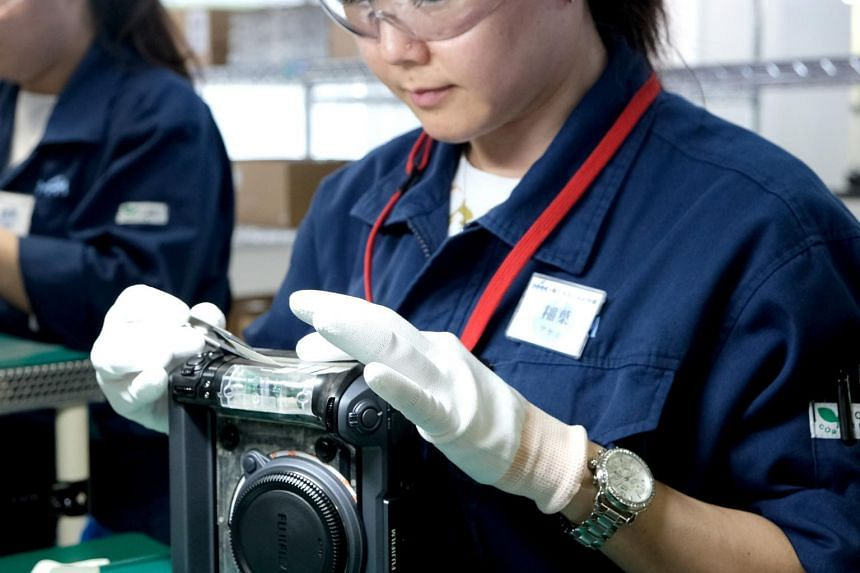 A technician putting the finishing touches to Fujifilm's latest medium-format mirrorless camera GFX 100 at Fujifilm's factory situated in Taiwa, Japan.
