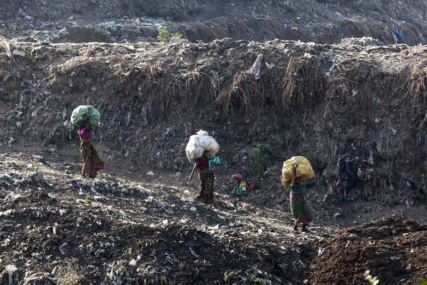 Indian rag pickers carry sacks of sorted recyclable materials at the Ghazipur landfill site in the east of New Delhi on April 14, 2018.