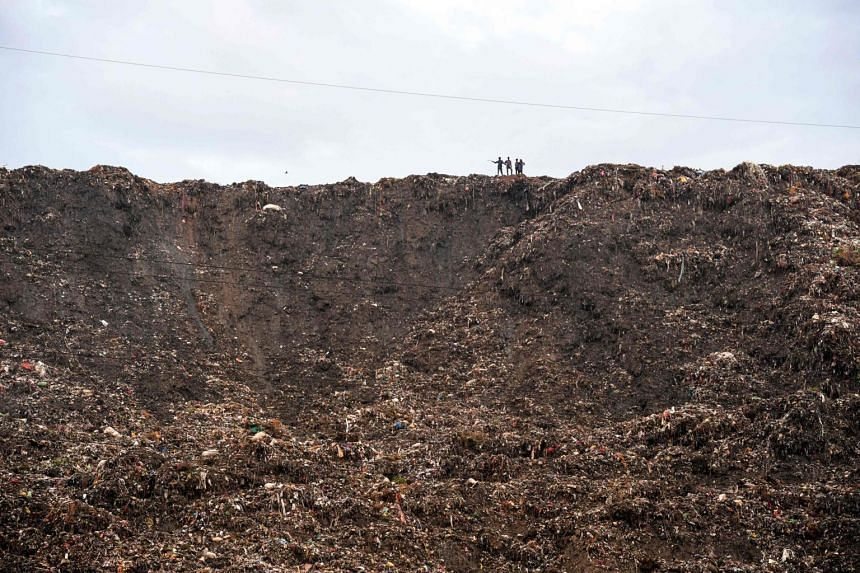 People stand atop a garbage landfill in Ghazipur area in India's capital New Delhi on Sept 1, 2017.