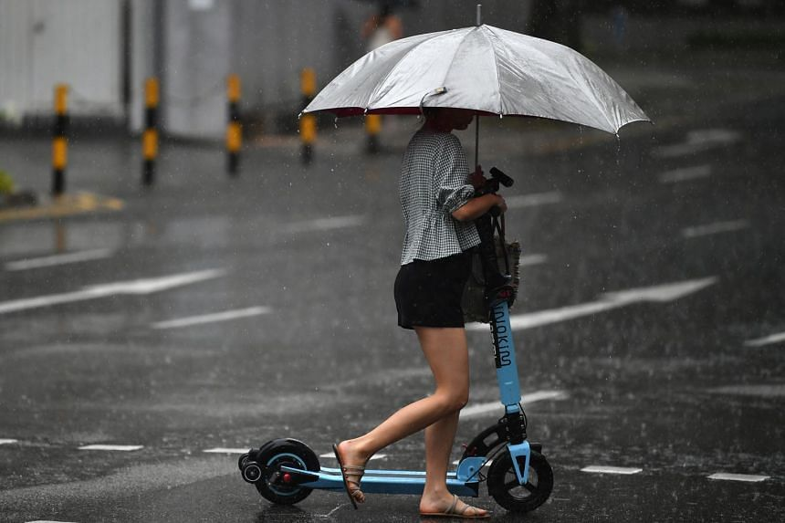 A pedestrian with an electric scooter crossing the road on June 3, 2019.