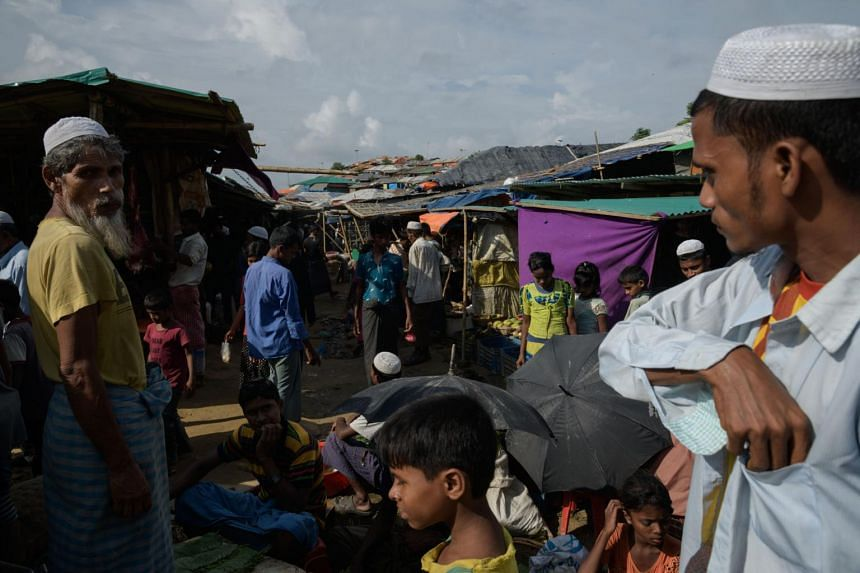 Rohingya refugees stand before a market on a road at the Kutupalong refugee camp near Cox's Bazar on August 10, 2018.