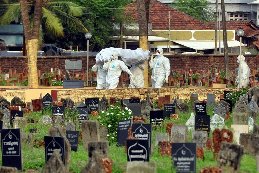 Doctors and relatives wearing protective gear carry the body of a victim who lost his battle against the brain-damaging Nipah virus, in Kerala, India, on May 24, 2018.